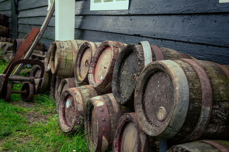 beer house: old oak barrels of beer were piled lie near the House Stock Photo