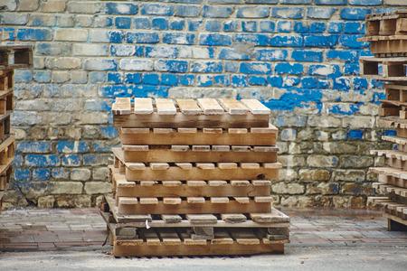 palet: Paletas de madera en el fondo de la pared de madera Foto de archivo