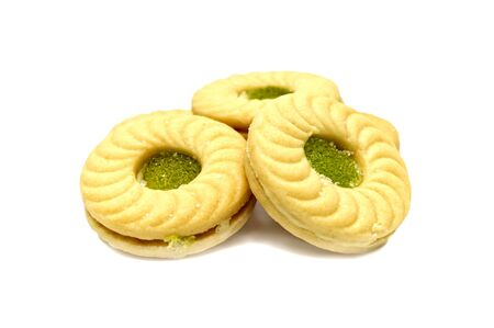 Biscuit sandwich butter cookies with cream and Kiwi&Apple flavoured jam. A stack of crunchy delicious sweet meal and useful cracker. isolated on white background. Soft focus. Archivio Fotografico