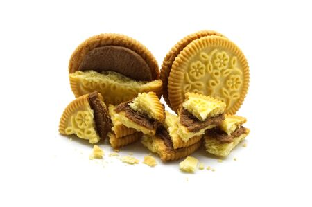 Sandwich cookies filled with coffee cream flavored. Some broken and crumbs of crunchy delicious sweet meal and useful cookie on white background.