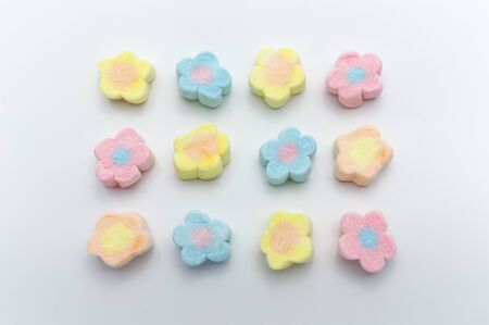 Pastel sweet flowers shape of marshmallows on white background. Фото со стока