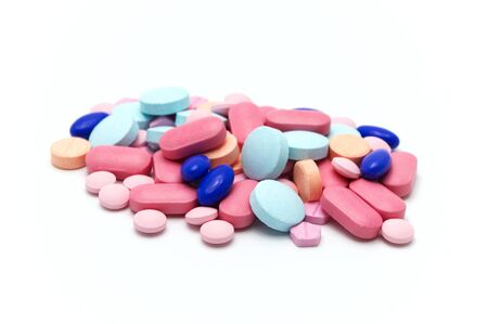 Many colorful medical pills on white background. Selective focus. Stock Photo