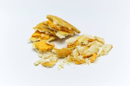 Biscuit and crumbs of sandwich cracker Cheese flavoured ,Cream and butter. Crunchy delicious sweet meal and useful cookies. On white background. Selective focus.