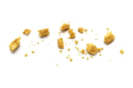 Scattered crumbs of butter cookies on white background.