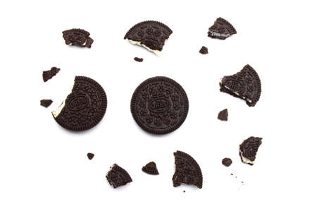 Oreo Biscuits with broken and crumbs isolated on white background. It is a sandwich chocolate cookies with a sweet cream is the best selling dessert in Thailand.