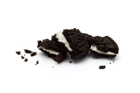 LAMPHUN, THAILAND - JULY 23, 2019: Oreo Biscuits with crumbs on white background. It is a sandwich cookies filled with chocolate cream flavored. The best selling dessert in Thailand. Selective focus.