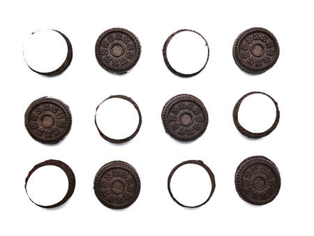 Sandwich chocolate cookies filled with a vanilla cream flavour biscuits in pieces of outside and inside isolated on white background.