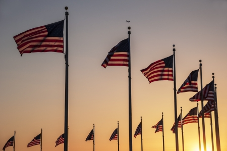 Flags around the base of the Washington Monument at sunset photo