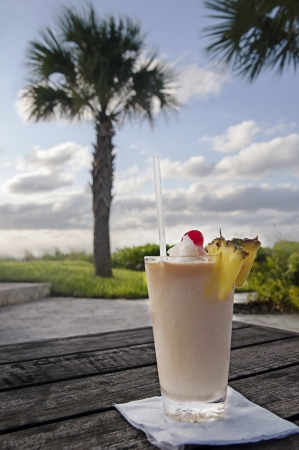 A tropical pina colada drink with pineapples and cherry with palm tree in the background photo