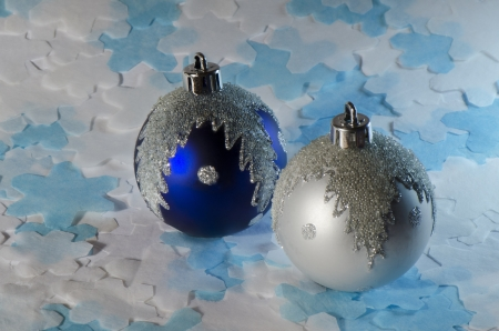 Blue and white Christmas balls on top of the blue and white cut-out snowflakes