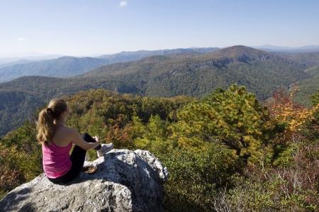 Young woman sitting on a rock, enjoying a mountain view