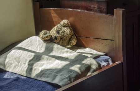 Old teddy bear lying in antique bed Stock Photo