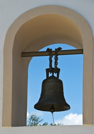 Church bell against backdrop of a blue sky