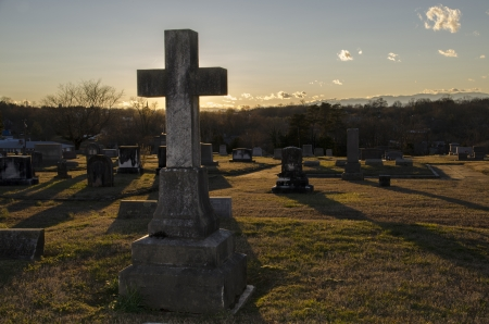 Old cemetery with a large cross at sunset Stock Photo