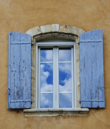 Old home exterior with clouds reflecting in a window Stock Photo