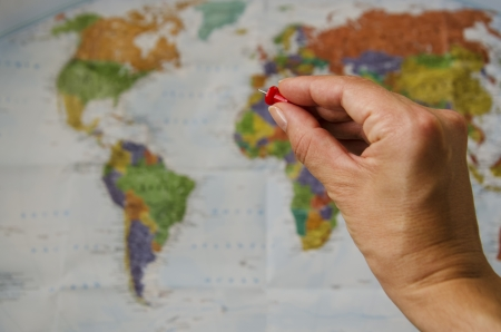 Hand with a pin pointing at a world map