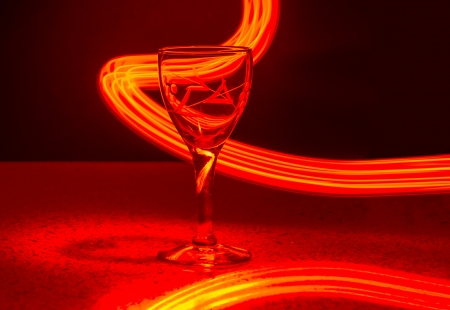 Liqueur glass over a black and red background