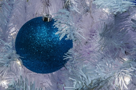 Blue Christmas ball against a white tree Stock Photo