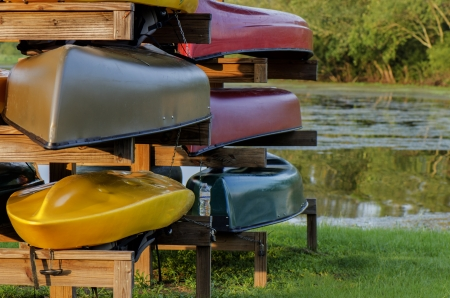 Rack with colorful canoes and kayak on the lake Stock Photo