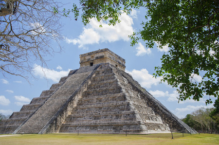 The Temple of Kukulkan  El Castillo  in the Mayan city of Chichen Itza, Mexico framed by trees