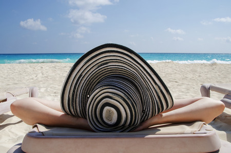Woman wearing a hat lying on the beach