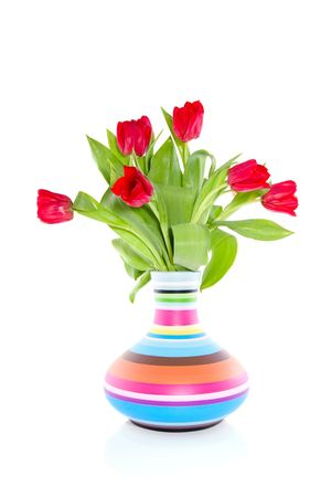 red tulips in a colorful striped vase isolated on white background