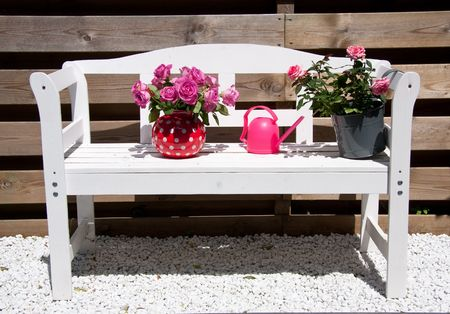 a white garden bench decorated with romantic roses