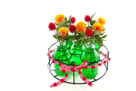 orange and red flowers in five glass vases in green liquid water photo
