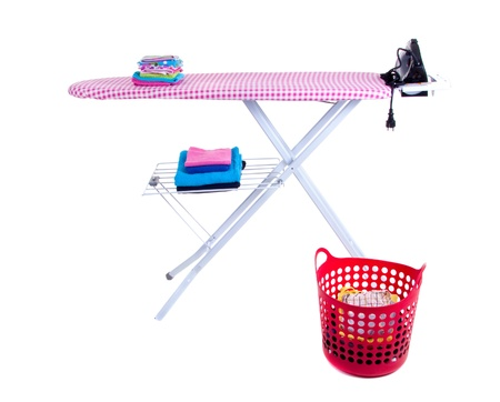 flat-iron and an ironing board with folded towels and clothes isolated over white