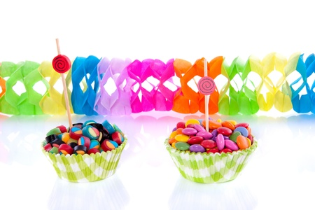 colorful little candy in  modern cupake molds with party streamers  isolated over white photo