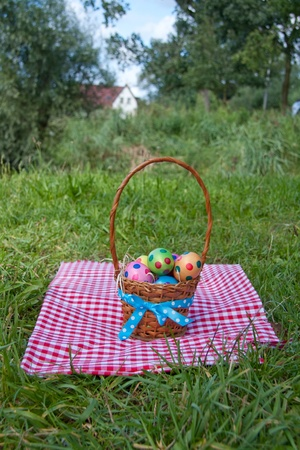 easter eggs in a wicker basket on a picnic cloth outdoors photo