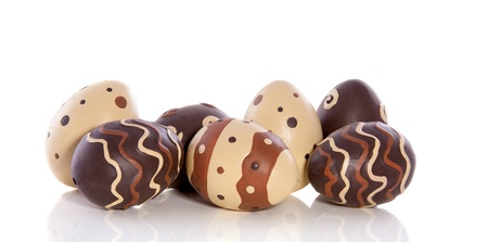 striped and dotted chocolate ceramic easter eggs isolated over white background