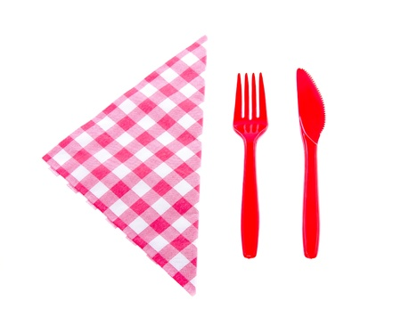 plastic knife and fork near a checkered red white napkin isolated over white