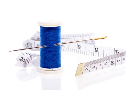 blue sewing thread with needle and black and white measure tape isolated over white