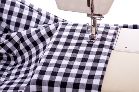a sewing machine with black and white checked modern fabric isolated over white photo