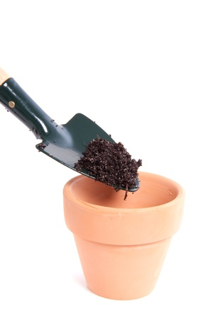 putting soil in a terracotta pot with a garden shovel isolated over white Stock Photo