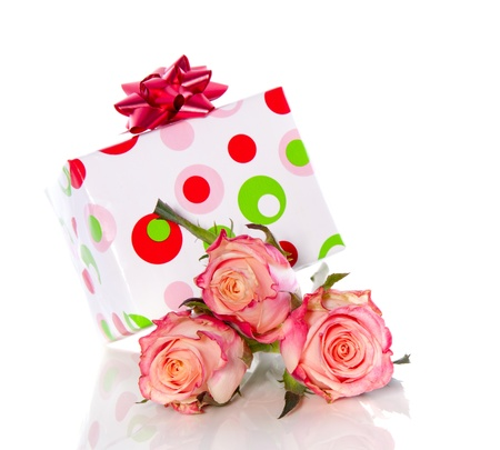 a cheerful gift on top of three pink orange roses isolated over white photo