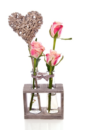 three pink roses in glass vases in a wooden rack decorated with a wicker heart isolated