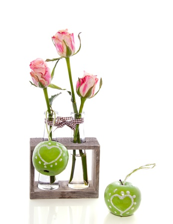 three pink roses in glass vases decorated with lovely wooden apples isolated over white photo