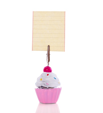 a colorful ceramic cupcake standard holing an empty text piece of paper isolated on white background photo