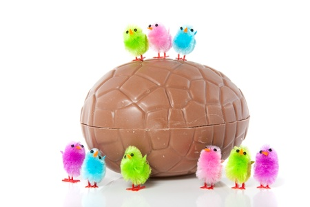 little colorful easter chicks above and in front of a big chocolate egg isolated over white