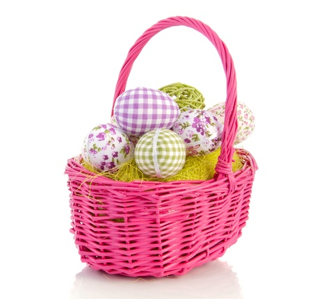 cheerful easter eggs in a pink wicker basket isolated over white background