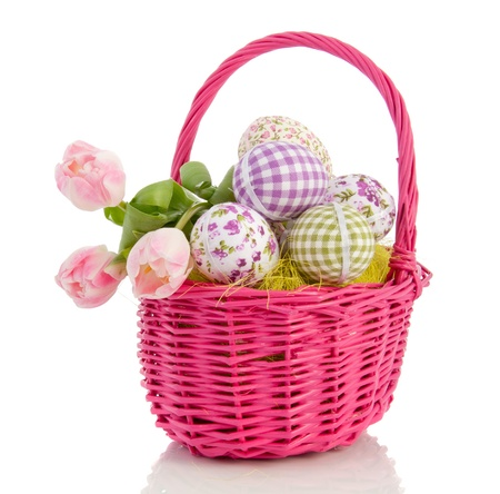cheerful easter eggs and tulips in a pink wicker basket isolated over white background