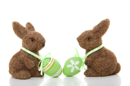 two brown bunnies with  easter eggs on their necks isolated over white
