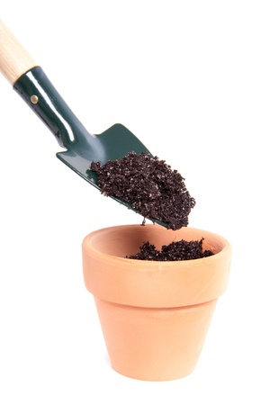 putting soil in a terracotta pot with a garden shovel isolated over white photo