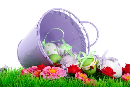 a purple bucket full of easter eggs on a green flowered lawn against a blue sky