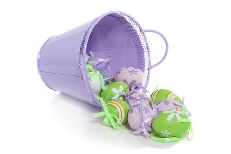 colorful painted easter eggs coming out of a purple bucket isolated over white photo