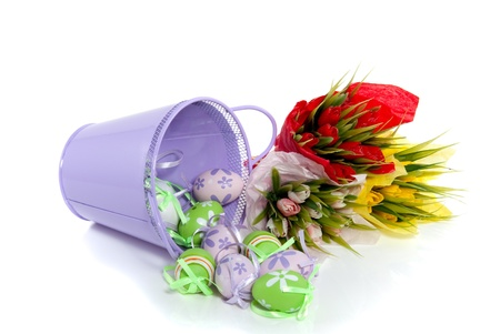 colorful painted easter eggs coming out of a purple bucket and bouquets of tulips  isolated over white