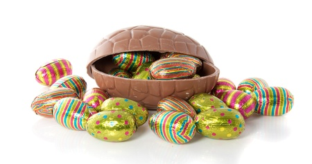 a big brown chocolate easter egg with many colorfully eggs in front and in the egg isolated over white Stock Photo