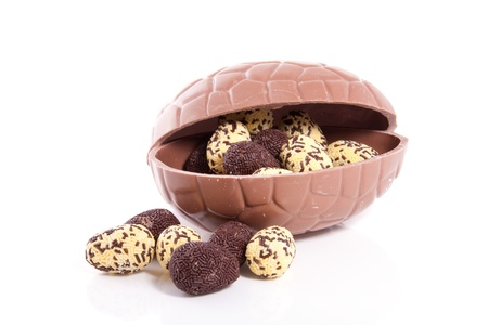 little sprinckled sweet eggs in a big chocolate easter egg isolated over white photo